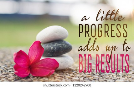"Holistic health concept of zen stones with deep red plumeria flower on pebble top with motivational quotes ""A little progress adds up to big results ""."