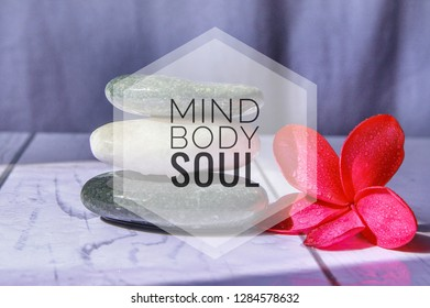 Holistic health concept of zen stones with deep red plumeria flower on blurred background. Text body mind soul.