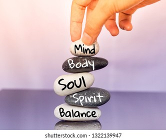 Holistic health concept of zen stones with female hand  on black and white background. Text mind body soul spirit balance.
