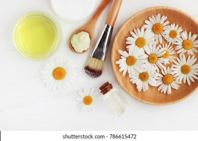 Holistic homemade herbal cosmetics with camomile, essential oils, bowls, facial cream, top view white wooden table.