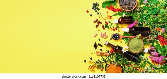 Holistic medicine approach. Healthy food eating, dietary supplements, healing herbs and flowers. Turmeric, dried lavender, spirulina powder in wooden bowls, fresh berries, omega acid capsules.