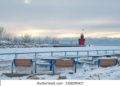 Holland Harbor red lighthouse in winter with ice on park benches and tables