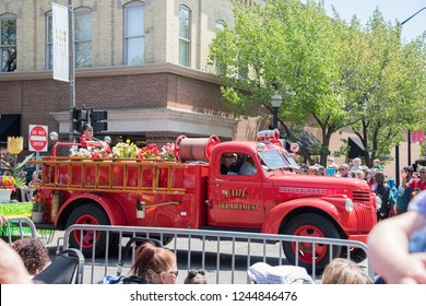 Holland, Michigan, United States-May 14,2017: Vintage fire engine truck filled with tulips in procession during a public parade with spectators in downtown Holland, Michigan.