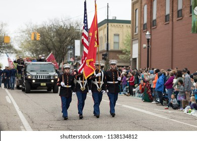 Holland, Michigan, USA - May 12, 2018 US Marines carrying the American Flag marching down the road at the Muziek Parade, during the Tulip Time Festival