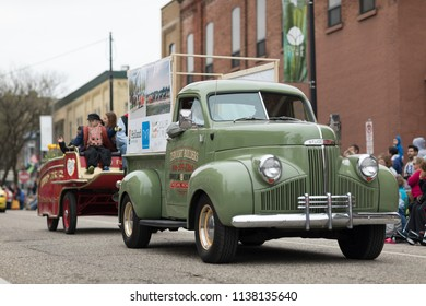 Holland, Michigan, USA - May 12, 2018 A classic green Studebaker truck with a sign that says Tervoort Builders, going down the road at the Muziek Parade, during the Tulip Time Festival