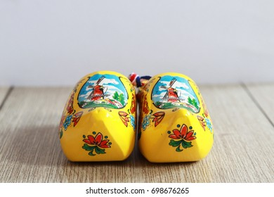 Holland yellow clog with windmills and Dutch pattern on wooden background