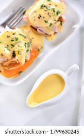 Hollandaise butter sauce in a gravy boat for breakfast served with Eggs Benedict- fried English bun, ham, poached eggs,