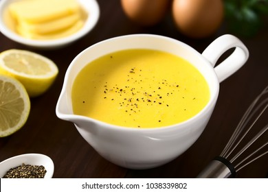 Hollandaise sauce, a basic sauce of the French cuisine, ingredients (egg, butter, lemon, pepper) and whisk on the side, photographed with natural light (Selective Focus in the middle of the image)