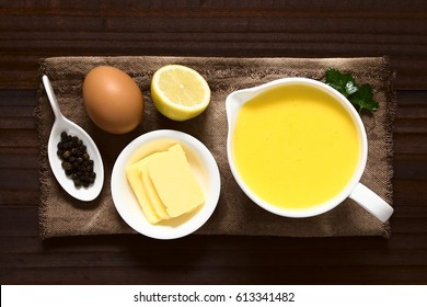 Hollandaise sauce, a basic sauce of the French cuisine, served in a sauce boat with ingredients (egg, butter, lemon, pepper) on the side, photographed overhead on dark wood with natural light
