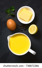 Hollandaise sauce, a basic sauce of the French cuisine, served in a sauce boat with ingredients (egg, butter, lemon, pepper) on the side, photographed overhead on slate with natural light