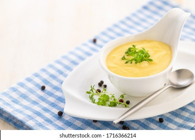 Hollandaise sauce. Classic French cuisine sauce. Emulsion sauce of butter and egg yolks with vinegar. Served in a gravy boat on a blue napkin. Close-up.