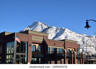 Holliday, Utah / U.S.A. - January 28th 2019: Harmons Food Store in Holliday downtown with view of Mount Olympus in background on sunny afternoon.