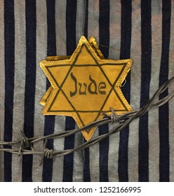 Hollocaust remembrance day, yellow star on gray and black fabric background. The word Jude means Jew in German.