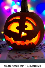 Hollowed and lit pumpkin in front of colorful background
