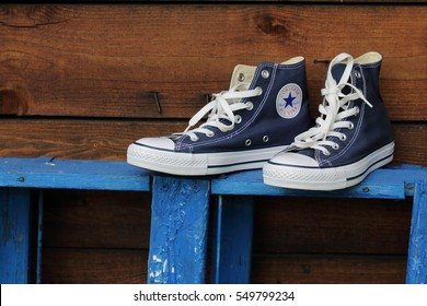 HOLLUM, DUTCH. 11NOV. 2016.: Converse shoe. Blue sneakers on wooden background with copy space. Top view.