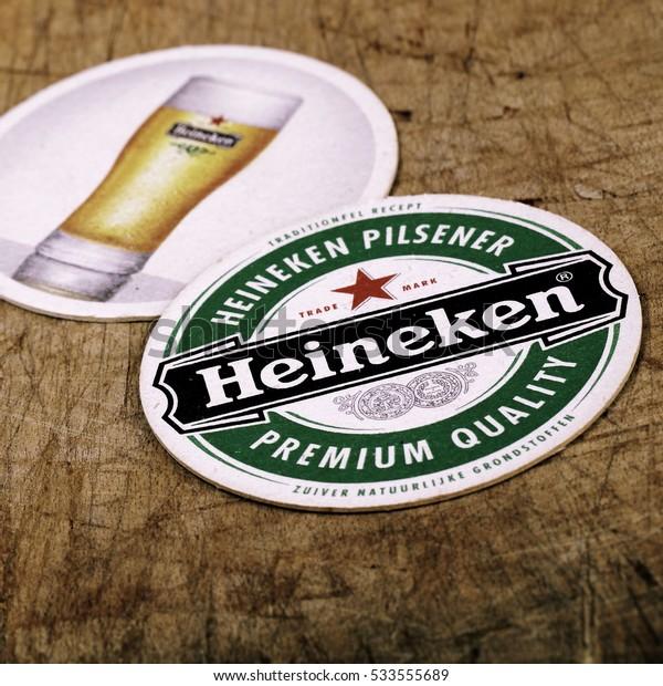 HOLLUM, HOLLAND - AUGUST 4, 2016.: Beer mats from Heineken Lager Beer in vintage background , it was first brewed by Gerard Adriaan Heineken in 1873
