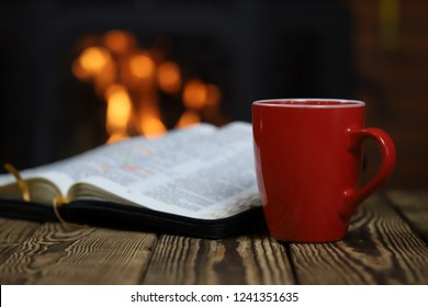 Holly Bible. Wood background. Bible and fireplace. Coffee.