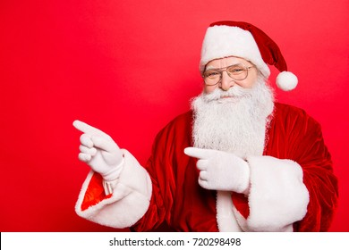 Holly jolly x mas, noel, newyear is soon! Be ready, prepare! Saint nicholas is showing on side with forefingers, isolated on red background. Sales, discounts, presents, gifts selling time!