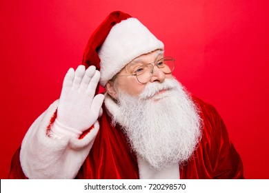 Holly jolly x mas, noel! Festive seosonal time. Funny cheerful saint nicholas in traditional head wear shows hand on ear gesturing with arm, gifts and presents list, isolated on red background