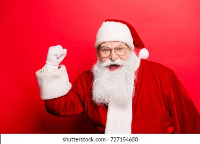 Holly jolly x mas and noel, confidence, magic, triumph concept. Cool funny playful grandfather with wide open mouth, comic grimace, fooling around isolated on red background, shows win gesture