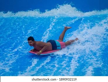 HOLLYWOOD BEACH, FLORIDA - DECEMBER 30, 2020: Teenager rides the wave on FlowRider at Margaritaville Hollywood Beach Resort