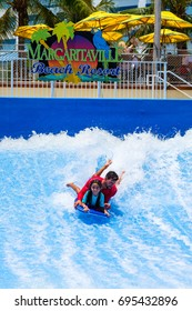 Hollywood Beach, Florida - July 6, 2017: Young visitor enjoying the wave riding flowrider attraction at the Margaritaville Resort, a popular tourist destination in Broward County.