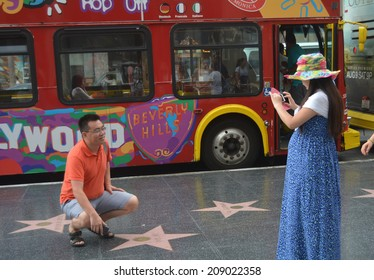 HOLLYWOOD, CA - AUGUST 3, 2014: A man crouches next to a celebrity star on the Hollywood, California Walk of Fame on August 3, 2014 as a woman stands nearby taking his photo.