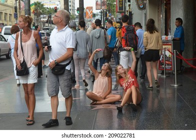 HOLLYWOOD, CA - AUGUST 3, 2014: Tourists stroll the Walk of Fame in Hollywood as two girls sit on the sidewalk, arms raised holding cell phones, taking photos of themselves near a celebrity star.