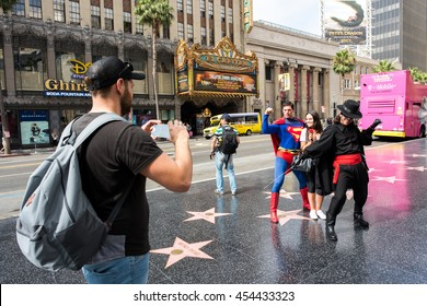 Hollywood, CA: July 16, 2016: Tourists taking photos of street performers in Hollywood.  Hollywood Boulevard is a major tourist destination in Los Angeles.