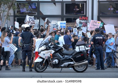 HOLLYWOOD, CA - NOVEMBER 13 2016: A police officer stands watch near his motorcycle as protesters rally against the election of Donald Trump on November 13, 2016 in Hollywood, California.