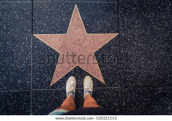HOLLYWOOD, CA - OCTOBER 12, 2016:.Tourist photographing her with an empty star on the Walk of Fame in Hollywood. Hollywood Walk of Fame features more than 2,500 stars with inscribed celebrity names