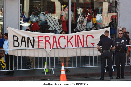 "HOLLYWOOD, CA - SEPTEMBER 18, 2014: Two policemen stand by as protestors display a large banner which reads, ""Ban Fracking"" during a demonstration in Hollywood, California on September 18, 2014."