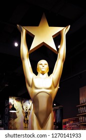 Hollywood, CA/ USA - July 26, 2018: Golden Oscar Statue holding gold star. Golden award or trophy is symbol of Success and Victory concept