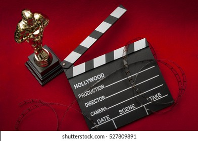 Hollywood film awards concept with shiny metallic movie award wrapped in celluloid film strip on red carpet with clapper board