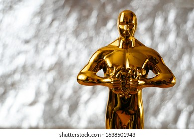 Hollywood Golden Oscar Academy award statue on silver background with copy space. Success and victory concept.