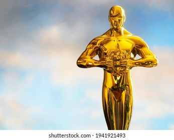 Hollywood Golden Oscar Academy award statue on sky background with copy space. Success and victory concept.