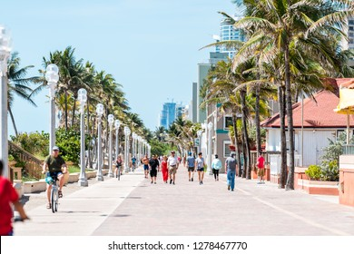 Hollywood, USA - May 6, 2018: Beach boardwalk in Florida Miami cityscape with sunny day and people walking on promenade coast by riding bikes exercising