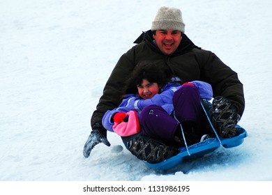 Holmdel, NJ, USA November 12, 2010 A father and daughter enjoy a down hill run while sledding in Holmdel, New Jersey