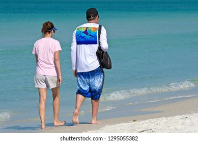 HOLMES BEACH, ANNA MARIA ISLAND, FL - May 1, 2018: Couple on vacation taking a walk on the beach  and enjoying a beautiful sunny day on the Gulf Coast of Florida.