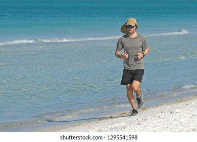 HOLMES BEACH, ANNA MARIA ISLAND, FL - April 29, 2018: Young Man taking an Early Morning Run on the Beach
