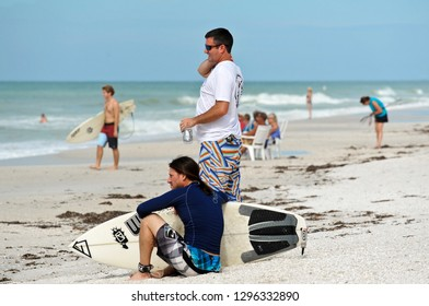 HOLMES BEACH, ANNA MARIA ISLAND, FL / USA -  October 4, 2013: Surfers on the Beach taking a break and watching their fellow surfers.