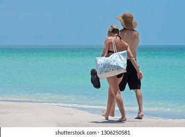 HOLMES BEACH, ANNA MARIA ISLAND, FL / USA -  May 1, 2018: Couple on vacation taking a walk on the beach  and enjoying a beautiful sunny day on the Gulf Coast of Florida.