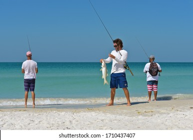 HOLMES BEACH, ANNA MARIA ISLAND, FL - May 1, 2018: A Group of Young Men on the beach Fishing in the Gulf of Mexico Enjoying a Beautiful Summer Day.