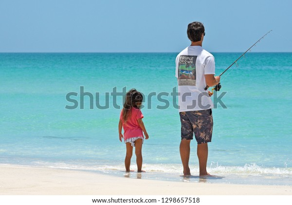 Holmes Beach, Anna Maria Island FL / USA - May 1, 2018: Father with Young Daughter on the Beach Fishing in the Gulf of Mexico