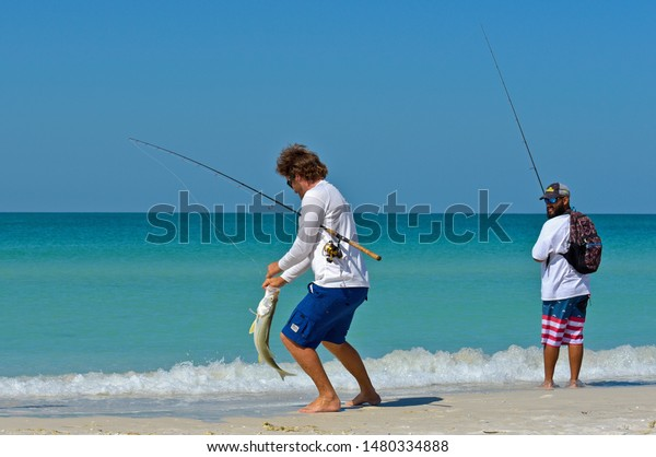 HOLMES BEACH, ANNA MARIA ISLAND, FL - May 1, 2018: Two local young men on the beach fishing in the shallow water of the Gulf of Mexico.