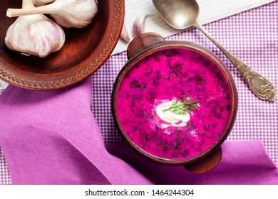 Holodnik - traditional Lithuanian (Russian, Ukrainian, Belorussian, Polish) cold beetroot soup with cucumber, boiled eggs and greens in rustic bowl. Flat lay, top view
