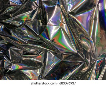 Holographic color wrinkled foil from real foil.Psychedelic or holographic background image.Very bright multicolor texture with all colors of rainbow.Colorful surface for luxury shiny metal look