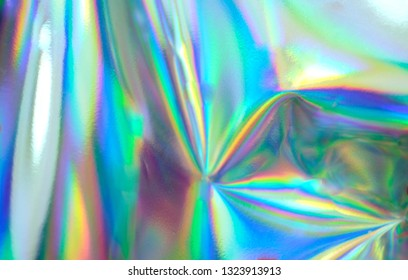 Holographic real texture, wrinkled foil in blue pink green colors with scratches and irregularities.