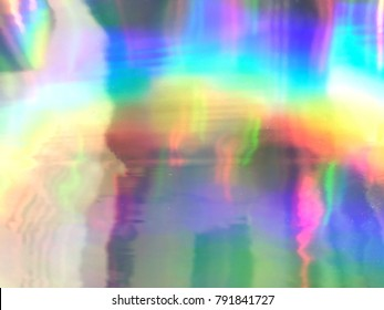 Holographic wrinkled abstract foil texture with multiple colors.