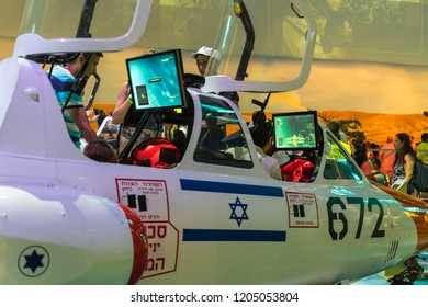 """Holon, Israel, 27 September, 2018 : Visitors sit in the cabin of the aircraft simulator and use it under the supervision of an army instructor at the army exhibition """"Our IDF"""""""